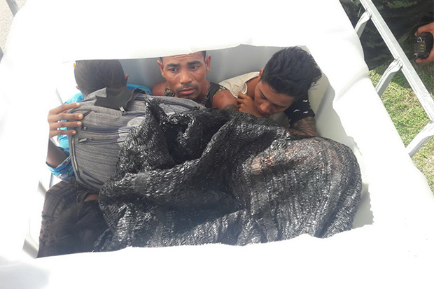 Three of the nine illegal migrants caught hiding in plastic containers on the back of a pickup in Sai Yok district of Kanchanaburi on Sunday afternoon. (Photo: Piyarat Chongcharoen)