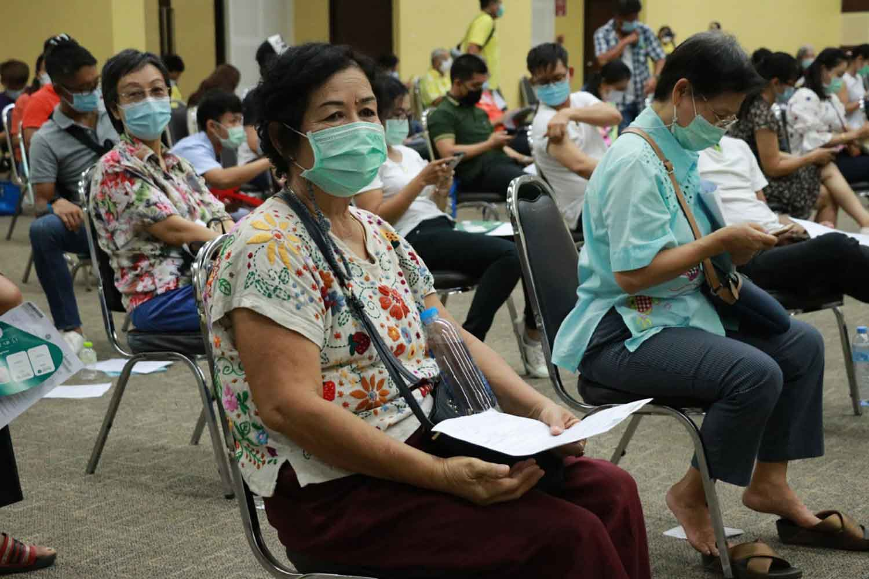 People wait for Covid-19 vaccination at Royal Park Ratchapruek in Chiang Mai province on Monday. (Photo: Panumet Tanraksa)