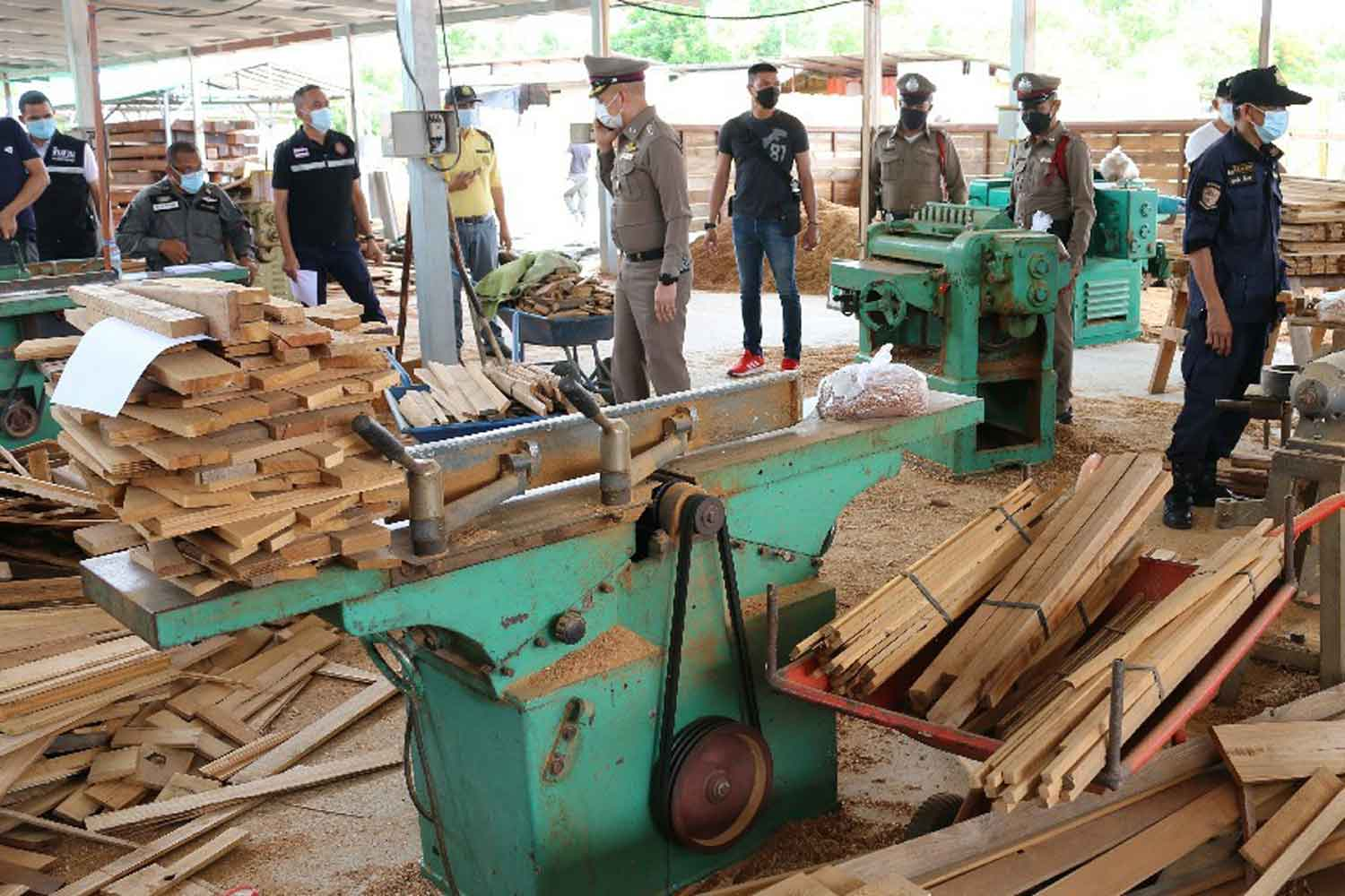 Police and officials from the Natural Resources and Environment Ministry search the Taweesap Kha Mai lumber plant on the outskirts of Kanchanaburi township on Monday. The owner and three workers were later arrested. (Photo: Piyarat Choncharoen)