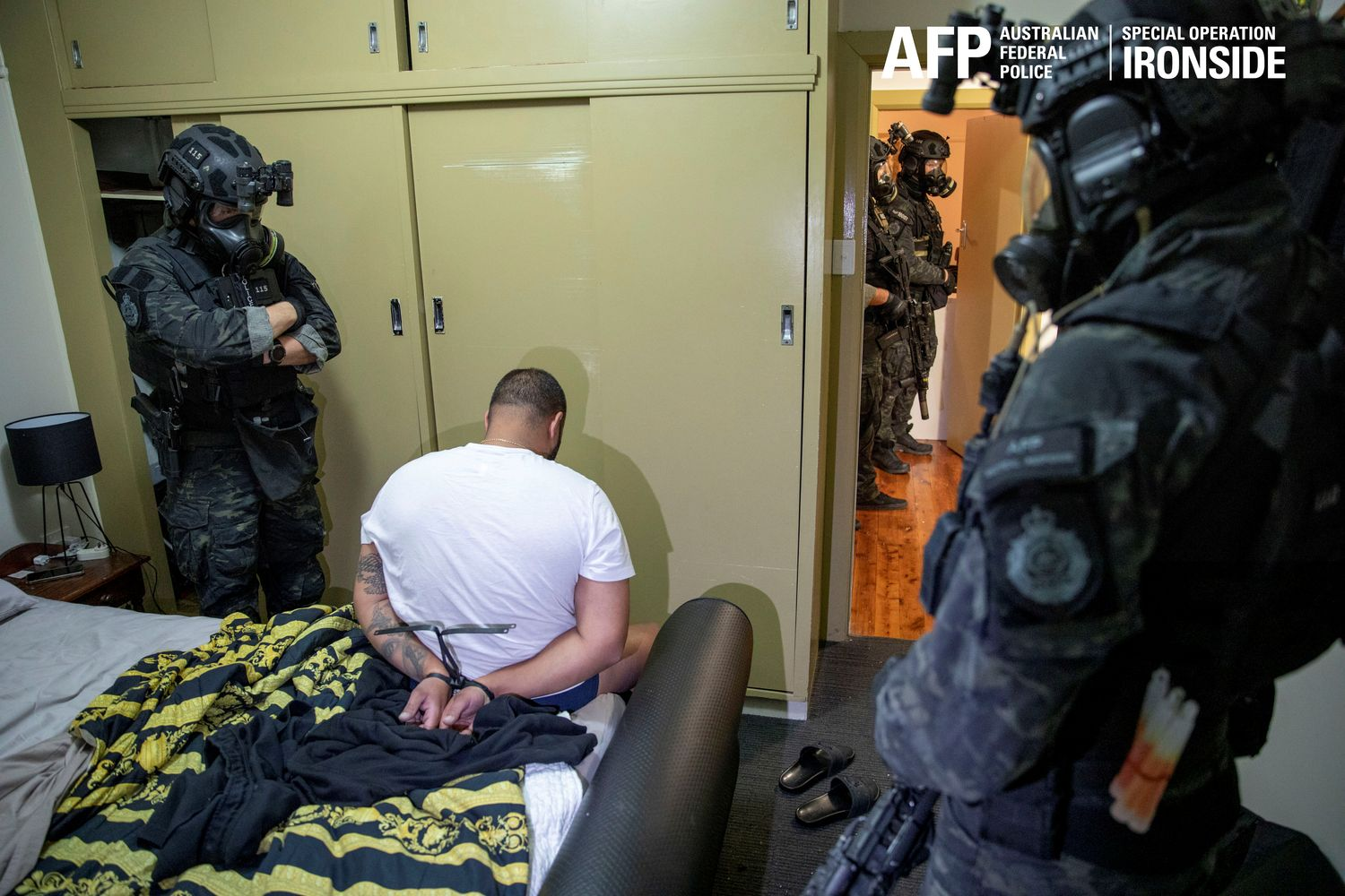 A person is detained by Australian Federal Police after its Operation Ironside against organised crime in this undated handout photo released Tuesday. (Australian Federal Police/Handout via Reuters)