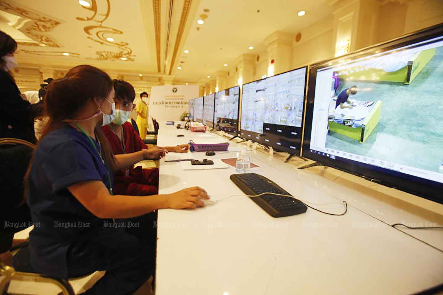 Medical workers monitor the condition of Covid-19 patients through surveillance cameras at the field hospital in the IMPACT convention and exhibition complex in Nonthaburi province on Tuesday. (Photo: Nutthawat Wicheanbut)