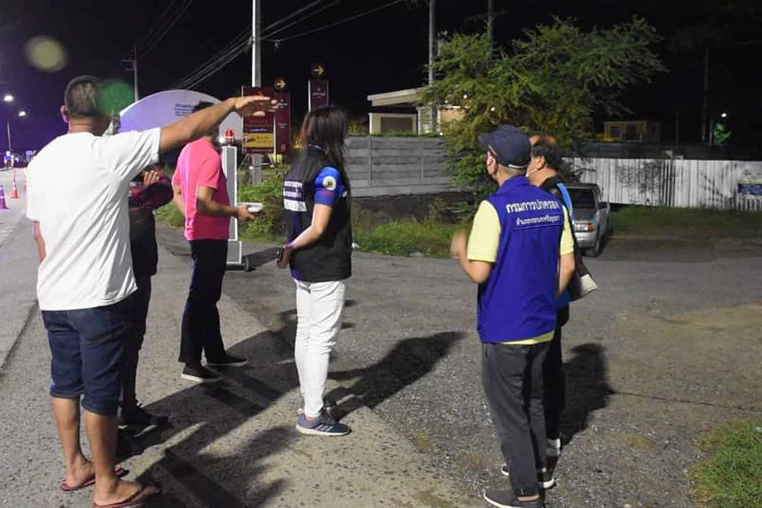Officials and local residents outside the construction workers' camp in Ayutthaya province locked down after 180 workers were found infected with Covid-19. (Photo: Sunthon Pongpao)