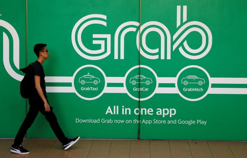 FILE PHOTO: A man walks past a Grab office in Singapore on March 26, 2018. (Reuters)