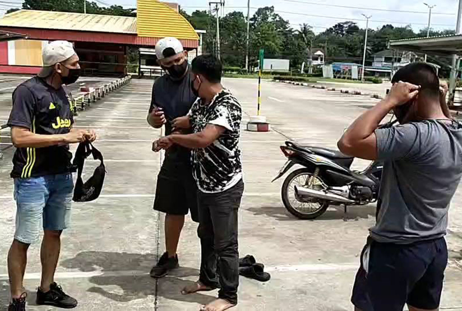 Myanmar guide Mong Fiew (centre) is arrested by plainclothes police in front of a convenience store in Sadao district, Songkhla, on Wednesday afternoon. (Photo: Assawin Pakkawan)