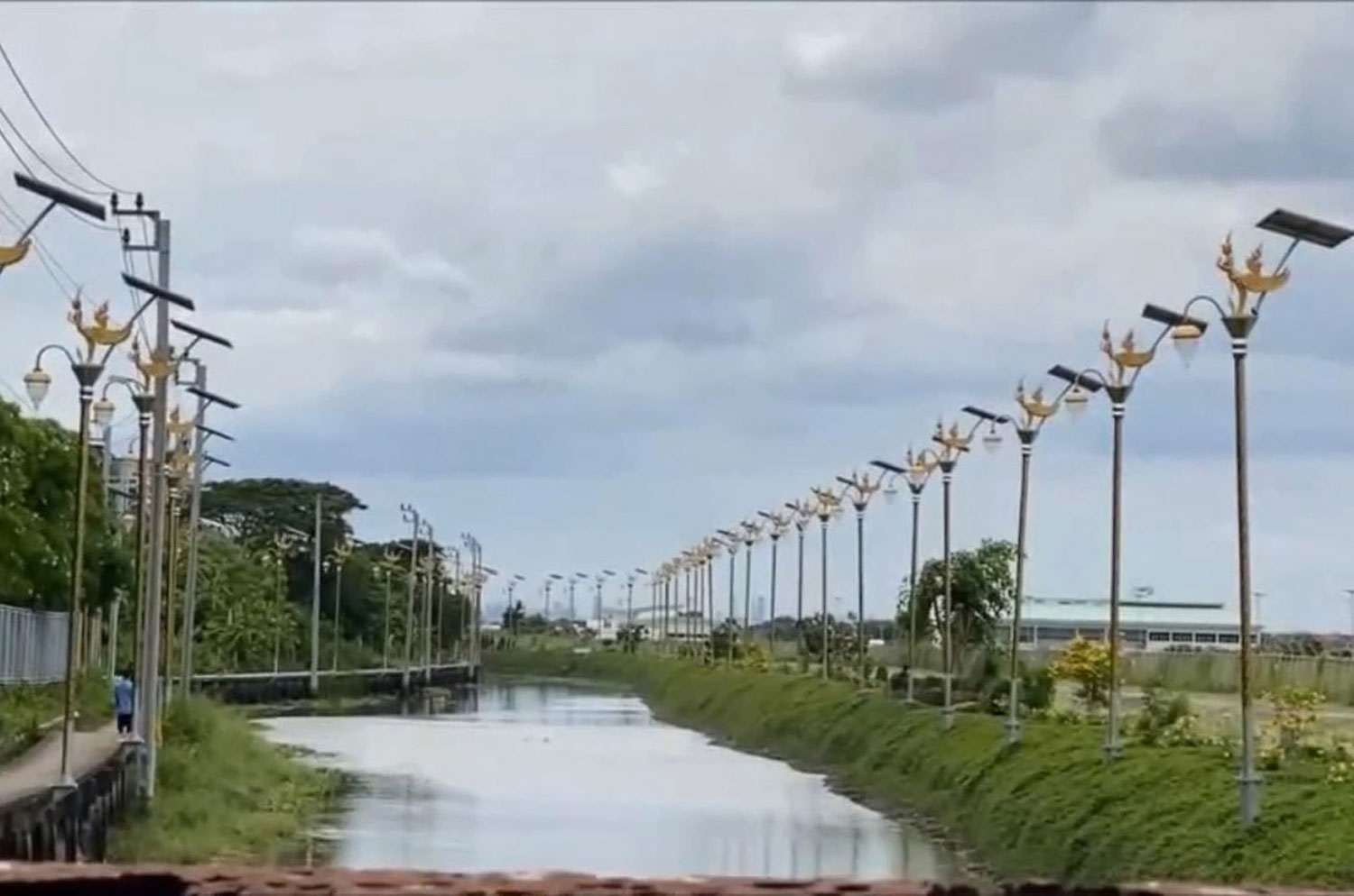 Closely spaced solar-powered lamp posts topped with mythical kinnaree figures line both sides of a flooded street in tambon Racha Thewa of Samut Prakan province. (Photo: Sutthiwit Chayutworakan)