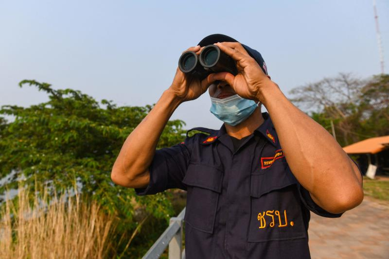 A member of a village security unit uses a pair of binoculars to look out over the Mekong river in Nong Khai province, bordering Laos, on March 15, 2021. (AFP file photo)