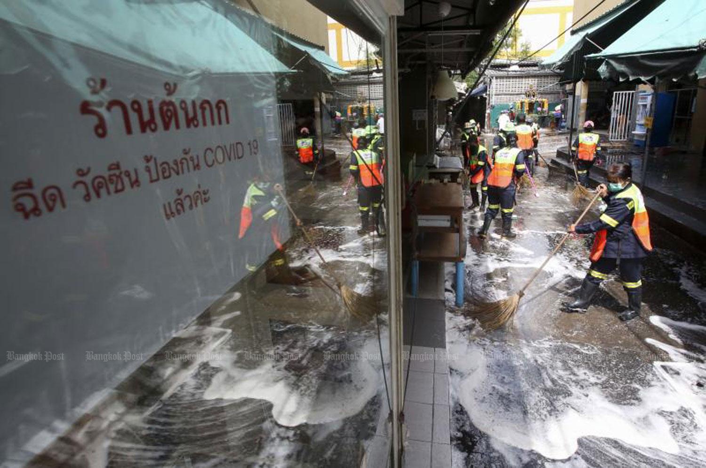 ฺWorkers from Bang Rak district office in Bangkok clean Lalai Sap market on Silom Soi 5. The popular market was closed for 3 days after a Covid-19 outbreak. (Photo: Pattarapong Chatpattarasill)