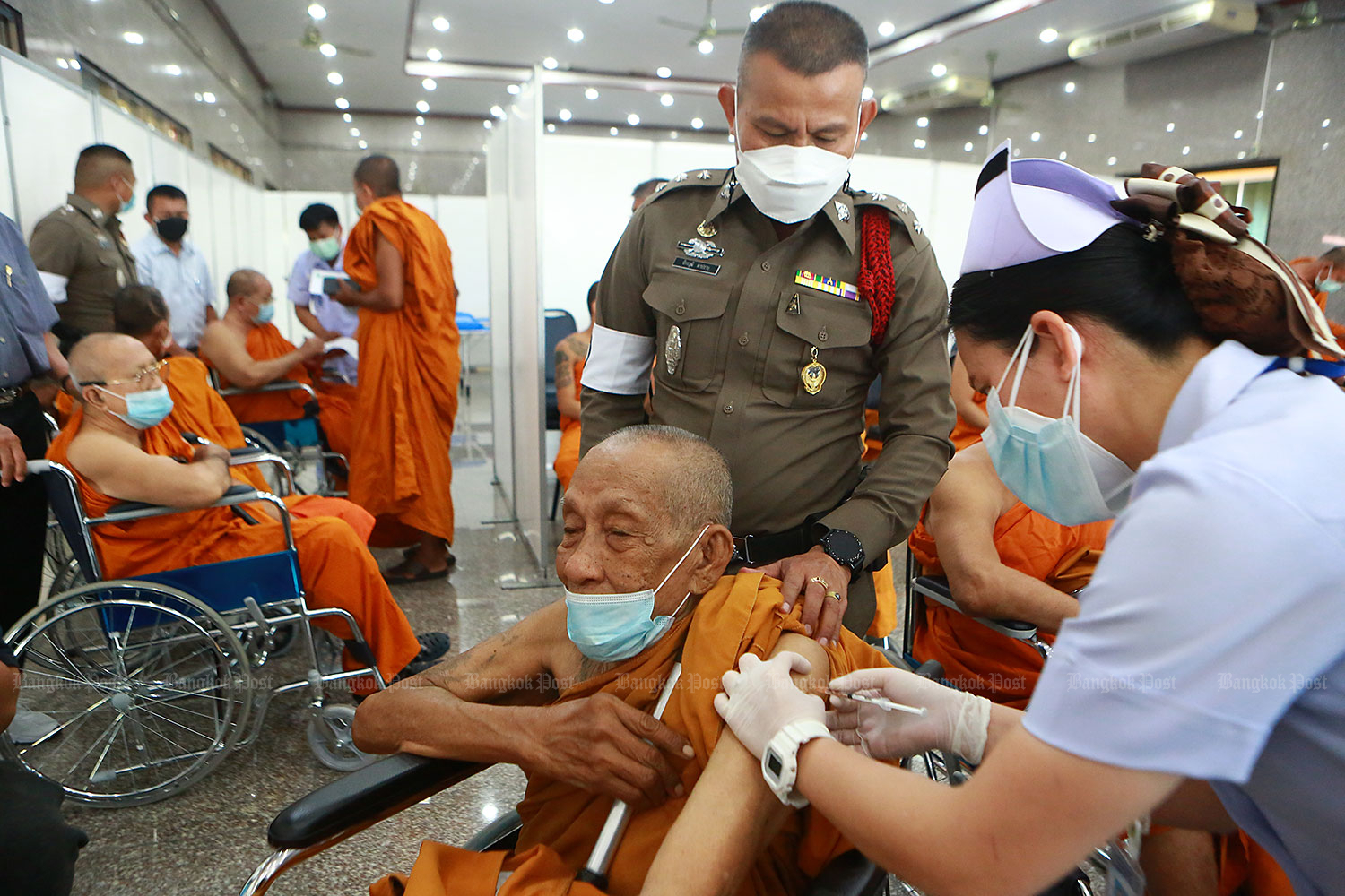 Easy does it: A nurse administers a Covid-19 vaccine jab to a monk at Wat Bang Phli Yai Klang in Samut Prakan. The temple has been added to a growing list of non-hospital vaccination points for the nationwide mass inoculation campaign. (Photo: Somchai Poomlard)