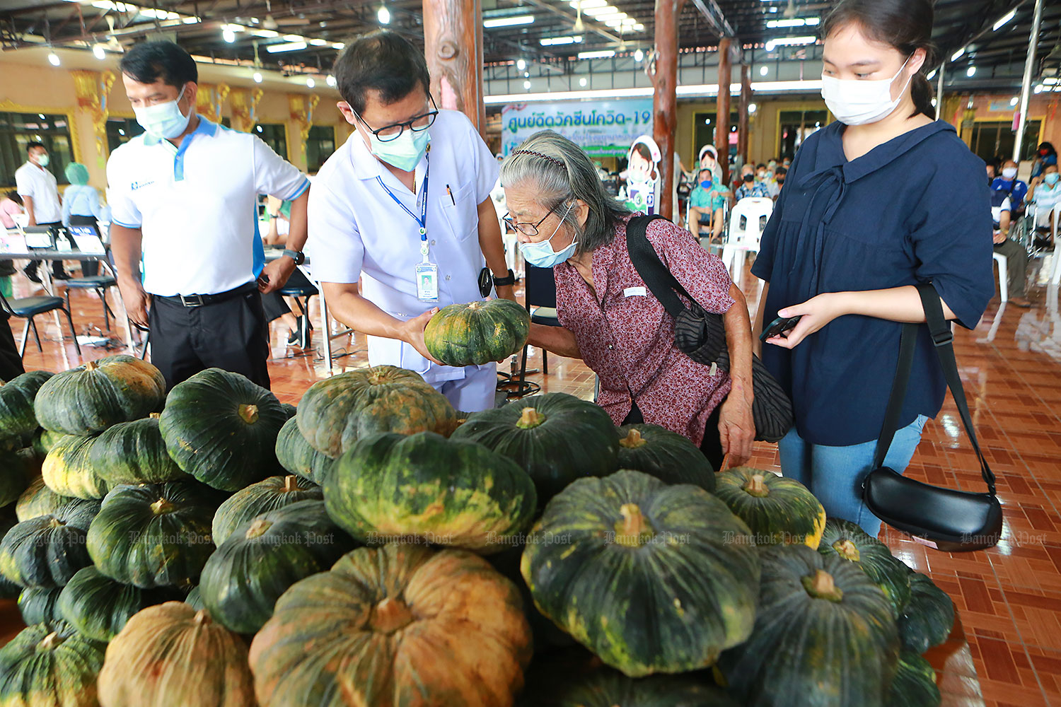 A medical worker selects a pumpkin for a woman after she received a Covid-19 vaccination at Wat Bang Phli Klang in Samut Prakan. The temple abbot has given away free pumpkins to encourage people to have their jabs. (Photo by Somchai Poomlard)