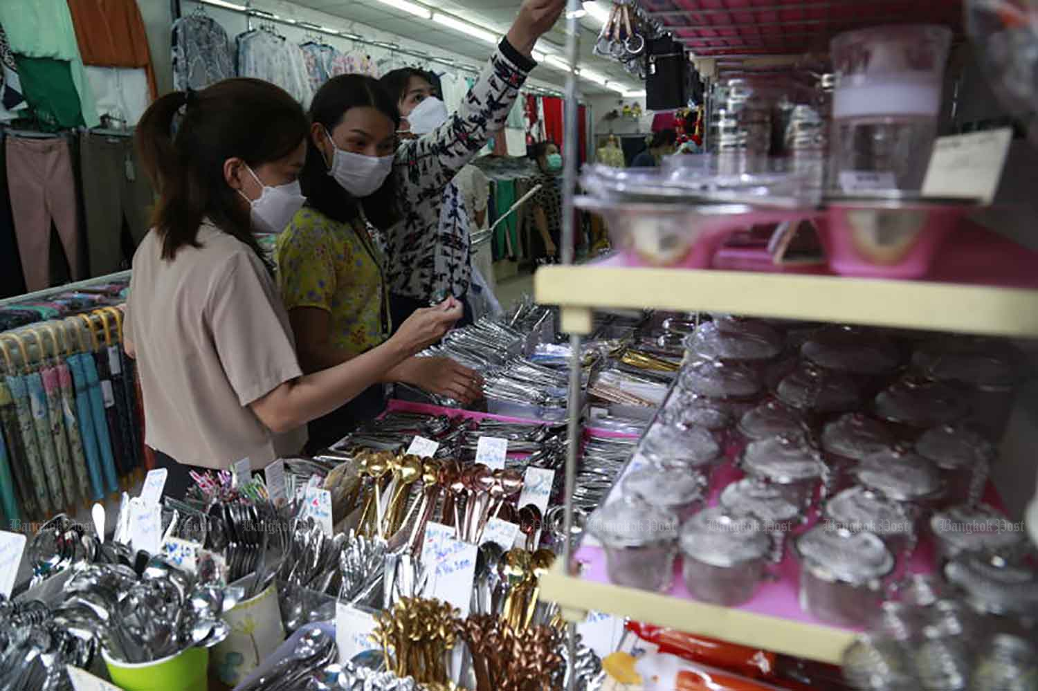Shoppers browse merchandise at a shop at Lalai Sap Market on Silom Road on Monday, where businesses have reopened after a week-long closure prompted by the detection of several Covid-19 infections. (Photo: Arnun Chonmahatrakool)