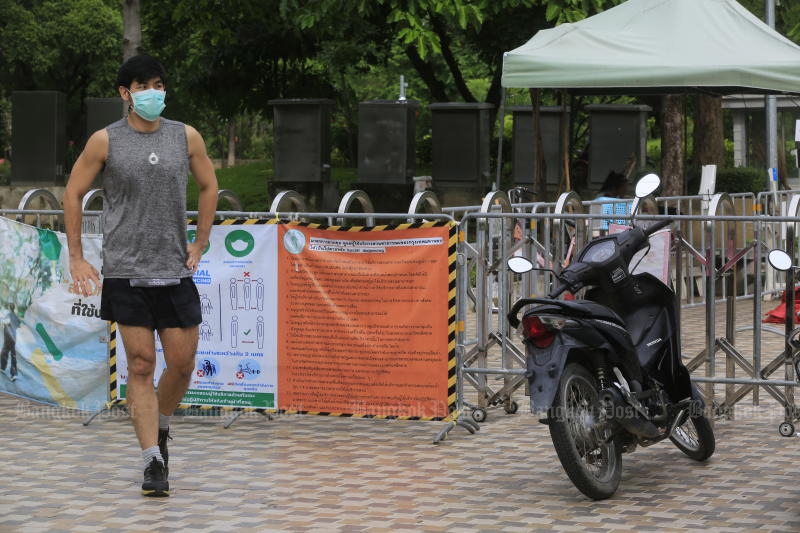 A disappointed jogger leaves Vachirabenjatas Park, or Suan Rot Fai, on Monday morning after arriving and finding the gates still closed. The city's parks finally reopened at 1pm for limited activities. (Photo: Pornprom Satrabhaya)
