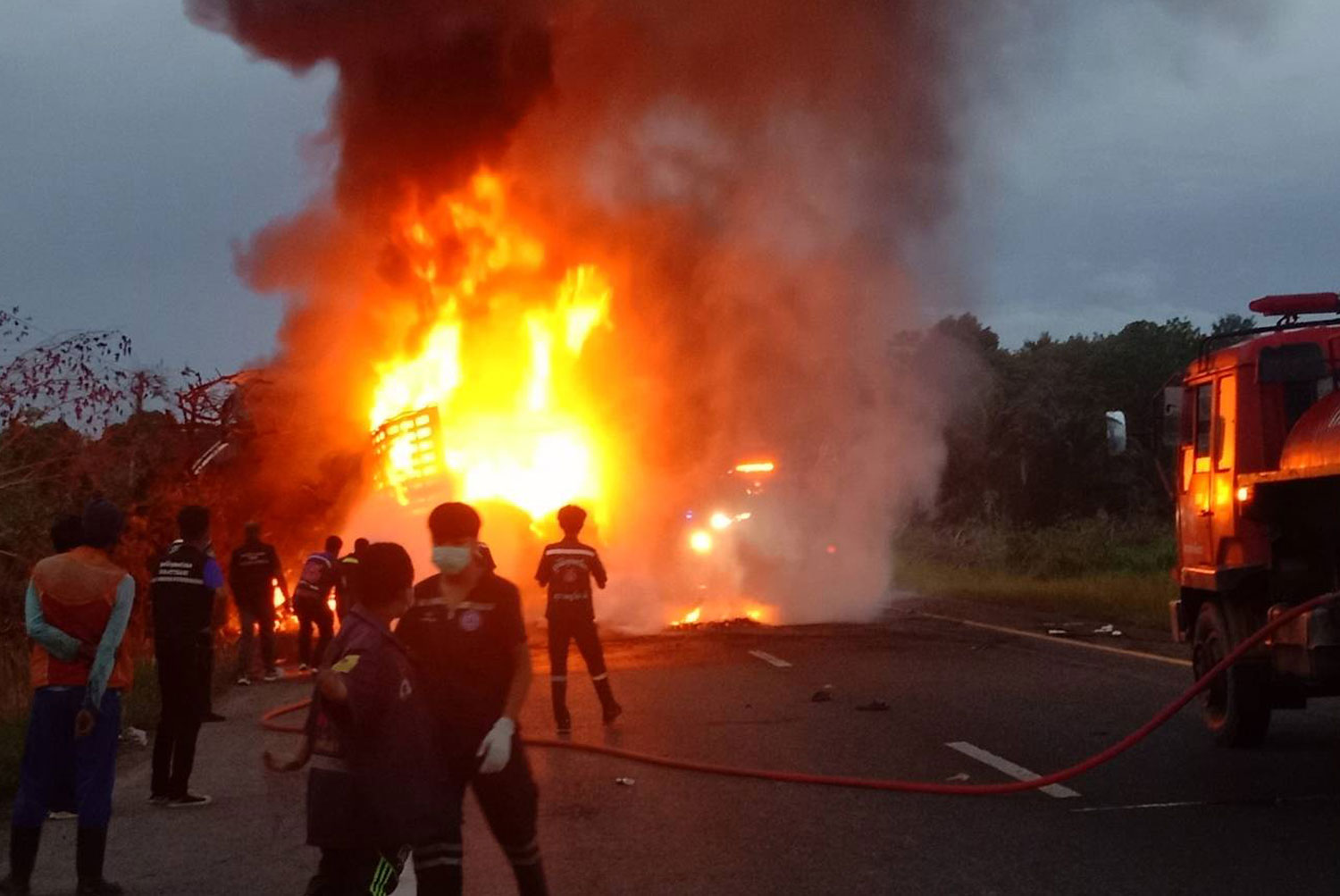 A truck carrying old car tyres bursts into flames after it hits a 10-wheel truck which rear-ends another trailer truck in Khian Sa district, Surat Thani. The crash left three people dead and one seriously injured. (Photo: Supapong Chaolan)