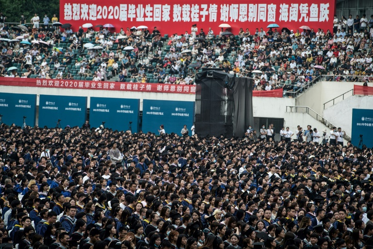 Almost 9,000 students, many of whom could not attend a graduation ceremony last year, gathered in Wuhan without face masks and social distancing.