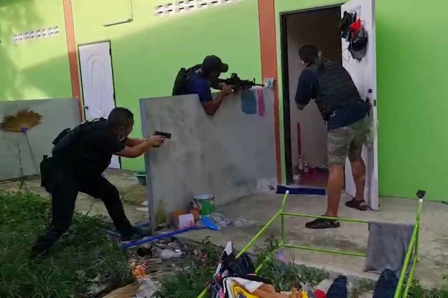 Crime Suppression Division police break into a room in Songkhla's Singha Nakhon district, rescue two hostages and arrest four alleged kidnappers, late Tuesday afternoon. (Photo: Assawin Pakkawan)