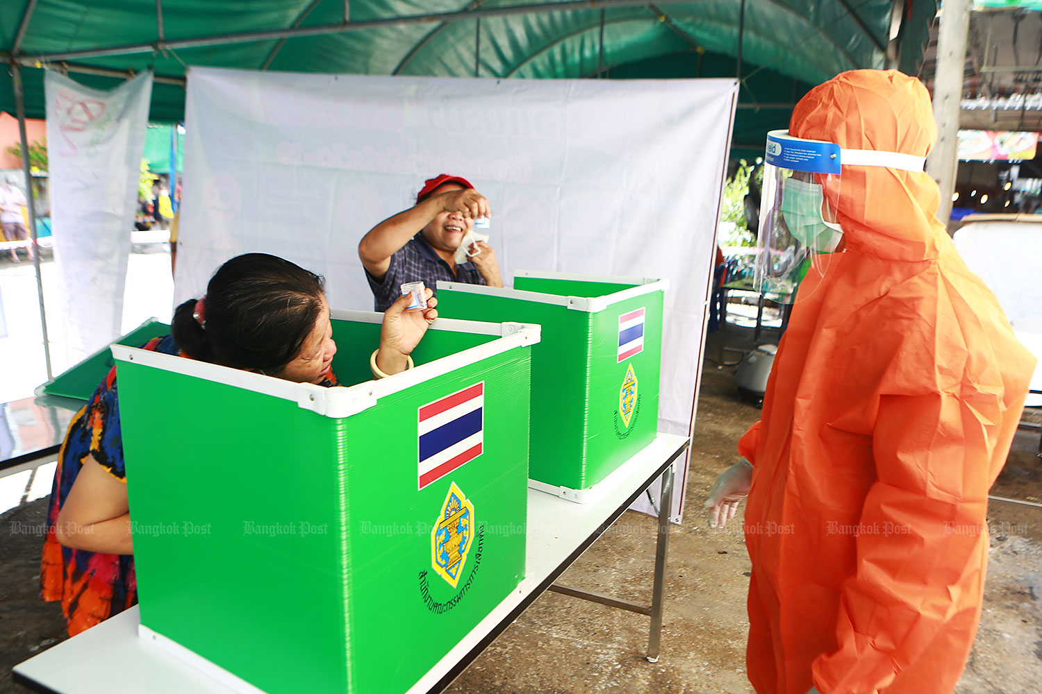 Will this do?: Women hold up saliva samples at improvised cubicles as a medical worker in full protective gear waits to collect them. The samples were for Covid-19 testing on people in at-risk groups in Yannawa district. (Photo: Somchai Poomlard)