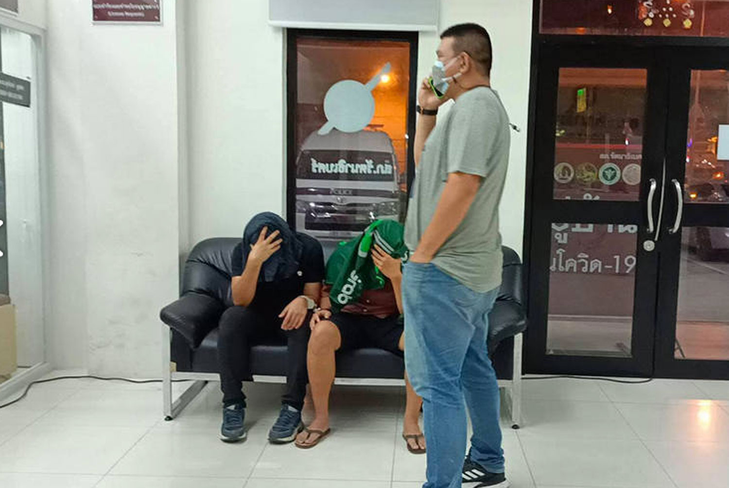 The two suspects, Cpl Vorasart Lailang, 31, of Khon Kaen and Nawatkorn Pongassaphon, 31, of Nakhon Ratchasima (both seated), cover their faces at Rattanathibet police station after their arrest on Wednesday night for extortion. (Photo: FM91bkk.com)