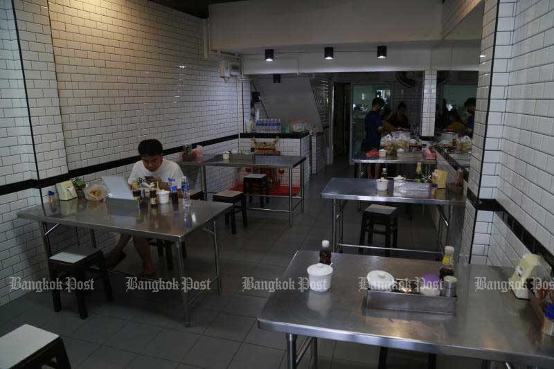 A man eats noodle at a shop in Bangkok on Sunday. City Hall eases restrictions at restaurants and other places from Monday. (Photo by Arnun Chonmahatrakool)