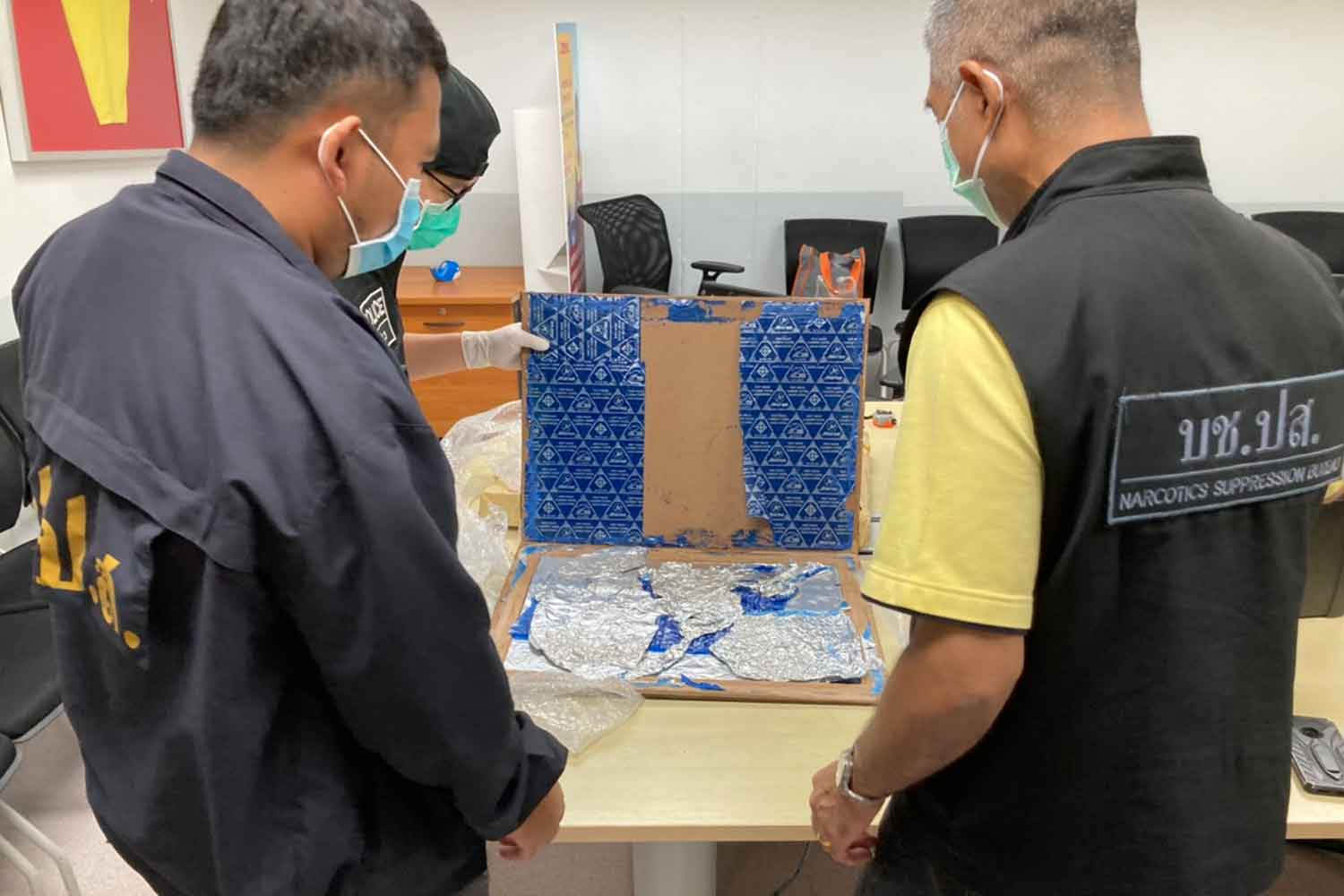 Anti-narcotic officials find thin packs of heroin hidden in the photo frame at a shipping company in Samut Prakan province on Monday. (Photo supplied)