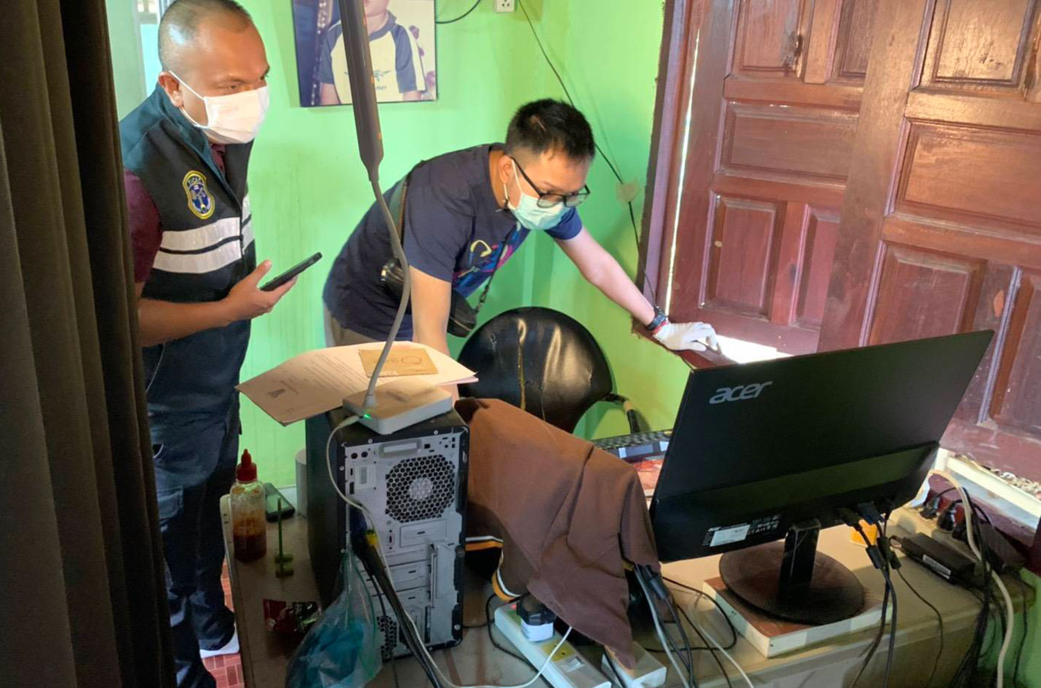 Police check a computer at a house in Mae Ramat district of Tak, where they found thousands of pornographic files featuring children and adults. (Photo supplied)