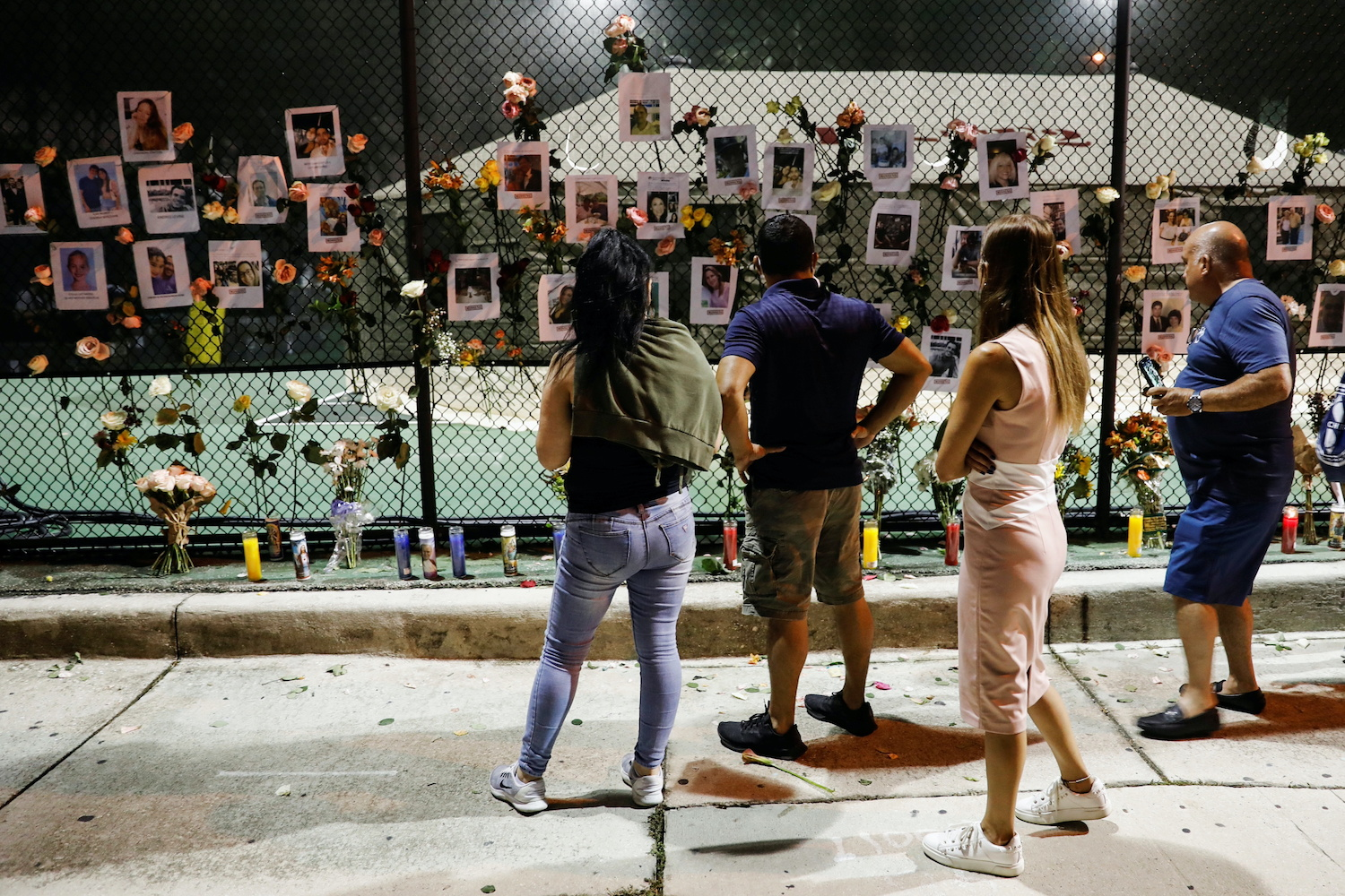 People look at flowers and pictures of missing people hanging on a fence at a memorial for victims of a partially collapsed condominium building in Surfside, near Miami Beach, Florida, on Friday evening. (Reuters Photo)