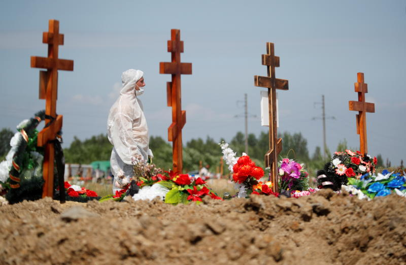 A gravedigger wearing personal protective equipment (PPE) as a preventive measure against the coronavirus disease (Covid-19) buries a person at a graveyard on the outskirts of Saint Petersburg, Russia on Friday. (Reuters photo)