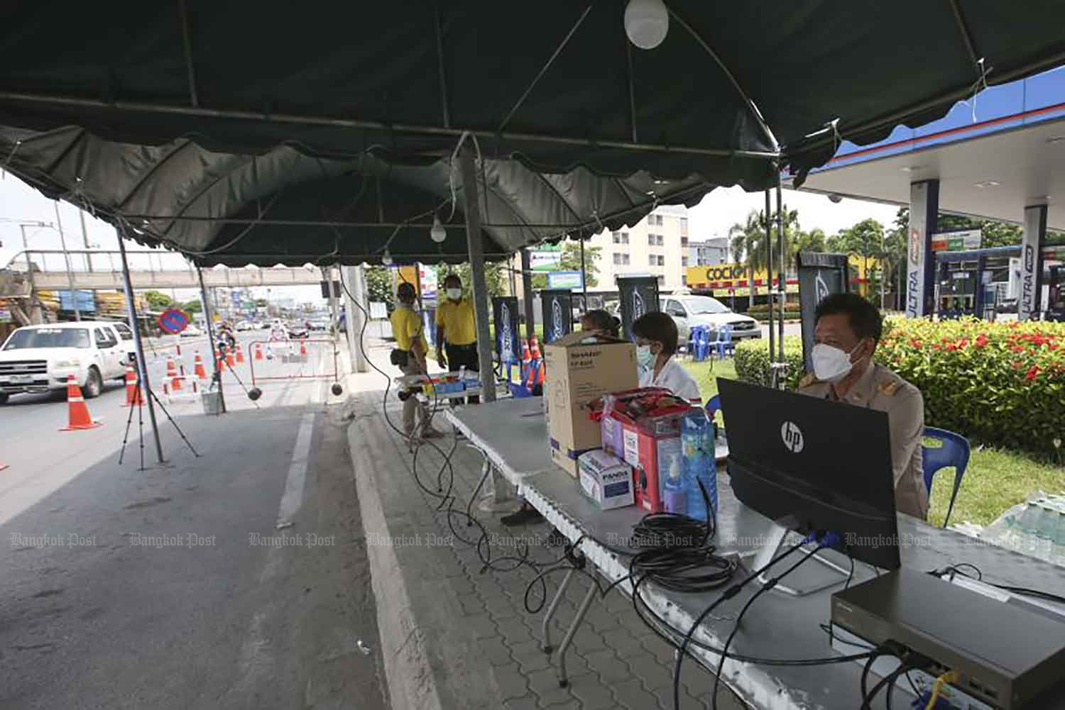 Officials man a checkpoint to enforce quarantine for construction workers to contain a cluster of Covid-19, in Pak Kret district of Nonthaburi on Monday. (Photo: Pattarapong Chatpattarasill)