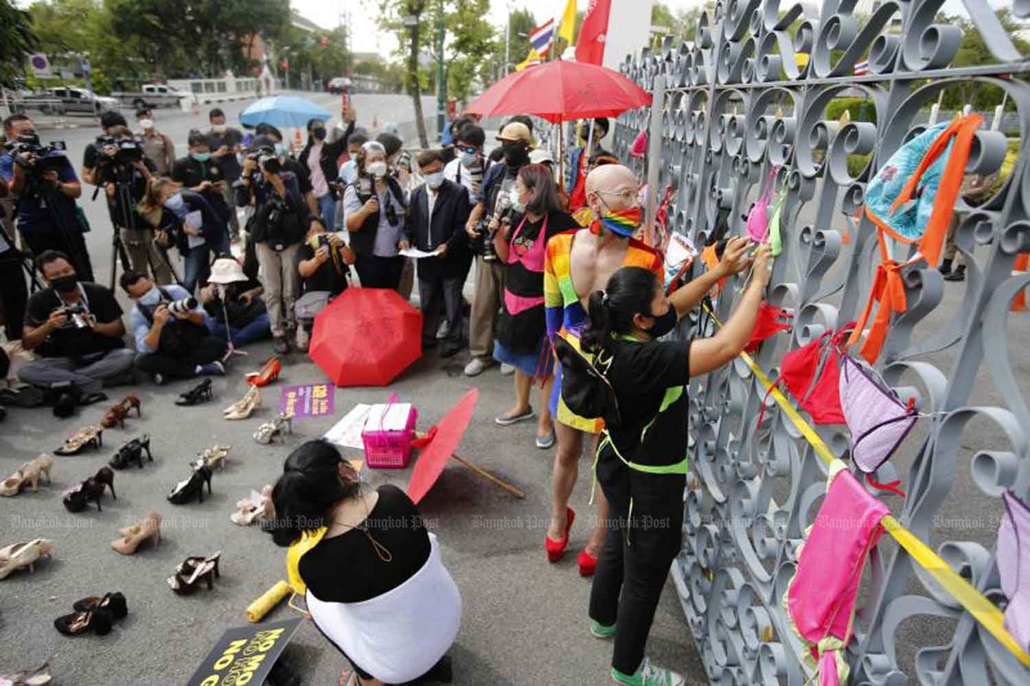 Representatives of nightlife workers display high-heels and hang bikinis on the gate of Government House during their rally demanding a monthly handout to survive the Covid-19 crisis after the government closed their workplaces early last year. (Photo: Wichan Charoenkiatpakul)