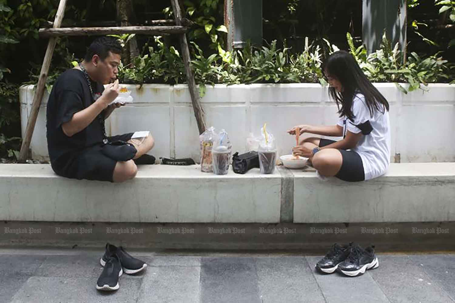People enjoy meals in a rest area outside CentralPlaza Lardprao shopping complex in Bangkok on Wednesday after measures banning dine-in services at restaurants and eateries were launched to contain the pandemic. (Photo: Pattarapong Chatpattarasill)