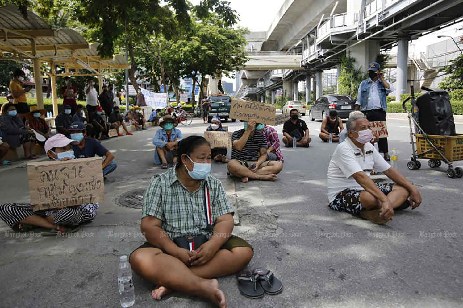 People from a community on Soi Sukhumvit 70/2 stage a sit-in on Sukhumvit Road near Bang Na intersection in Bangkok on Wednesday to demand that neighbours infected with Covid-19 receive treatment in hospital. They fear a community outbreak if the infected are forced to remain at home. They claim at least 20 people are infected. (Photo: Wichan Charoenkiatpakul)