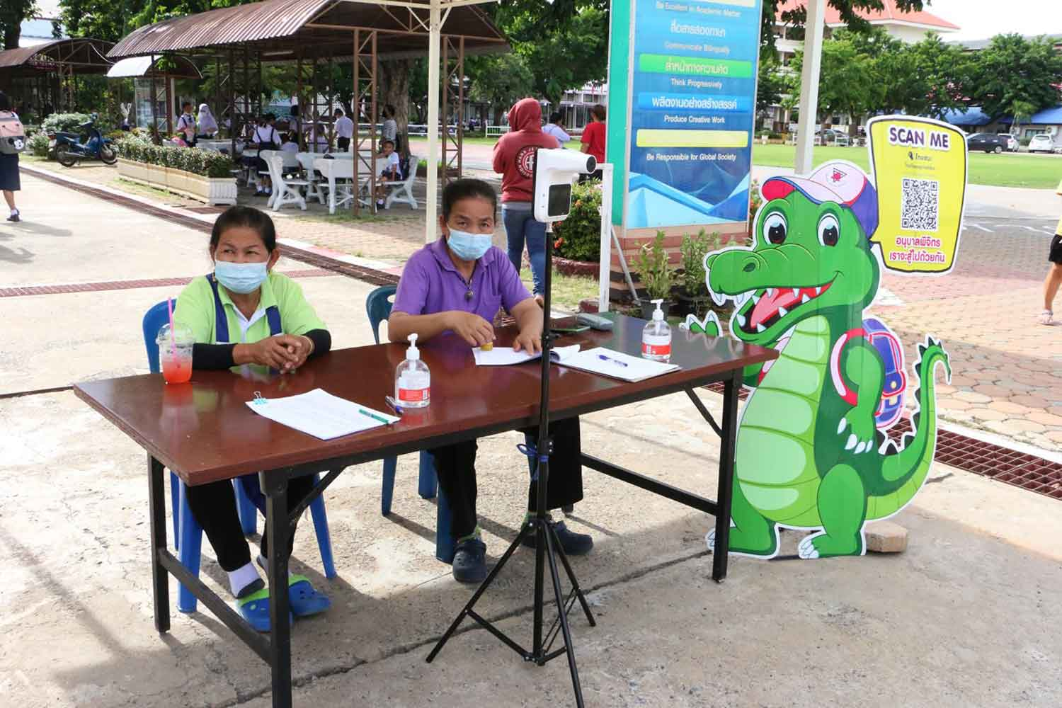 Staff members are at the health checkpoint of Anubanphichit School in Muang district, Phichit, before it turned to online teaching only on Thursday. (Photo: Sitthipoj Kebui)