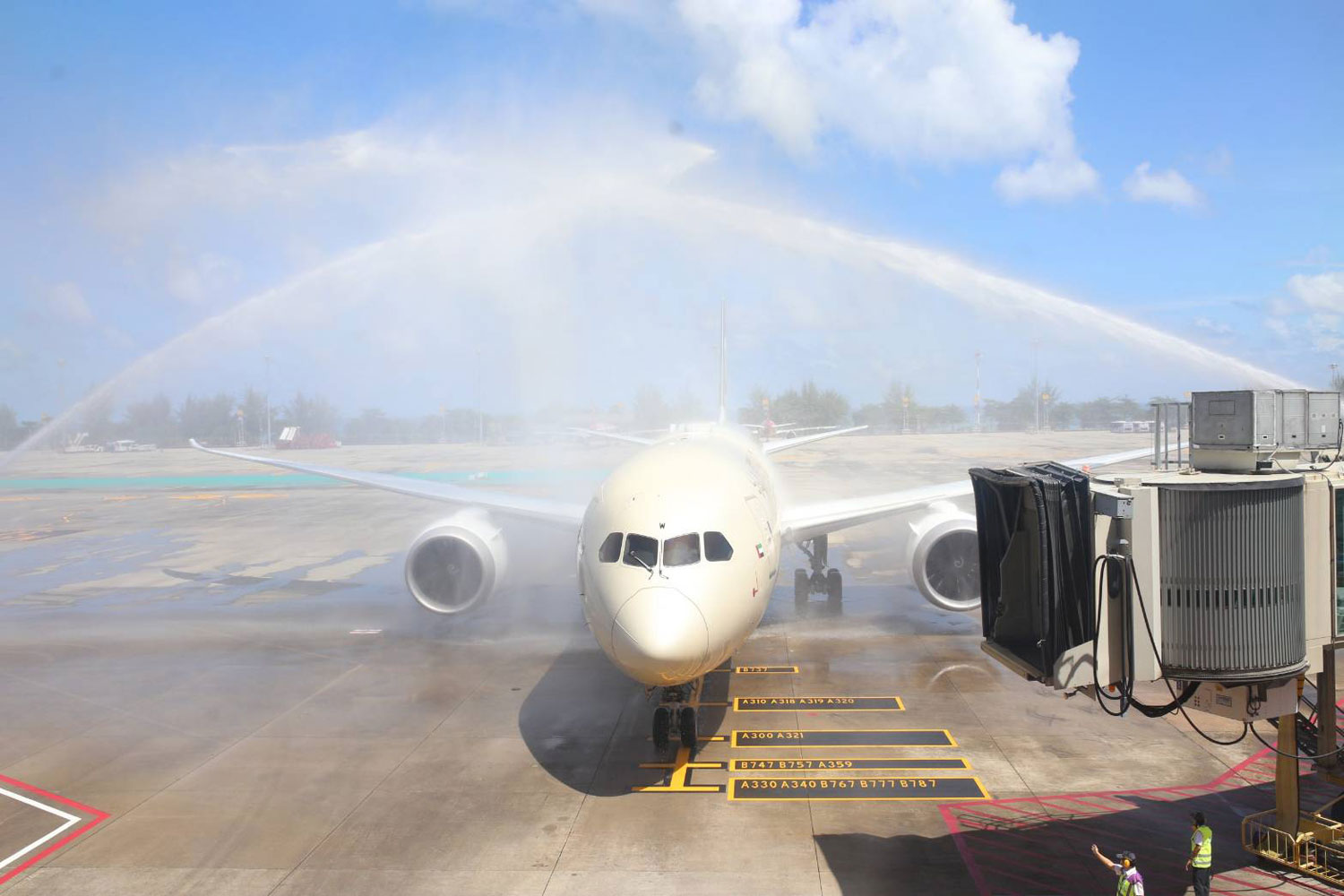 A flight carrying first 23 passengers from Abu Dhabi is welcomed through the water tunnel as it touches down the Phuket airport on Thursday morning. (Phuket airport photo)