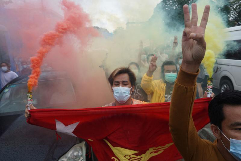 A protester holds the National League for Democracy flag during a flash mob demonstration against the military coup in Yangon on Thursday. (AFP photo)