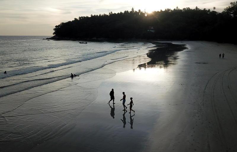 People walk on Kata beach on Thursday as Phuket reopens to overseas tourists. (Reuters photo)