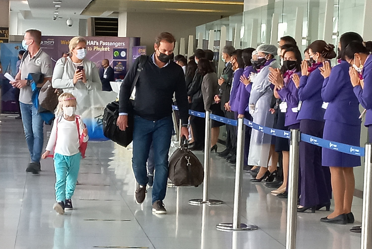 Tourists from Frankfurt are greeted by THAI staff at the Phuket international airport on Saturday morning. Three flights from European countries touched down at the airport to bring tourists to the island province under the Phuket sandbox scheme. (Photo: Achadthaya Chuenniran)