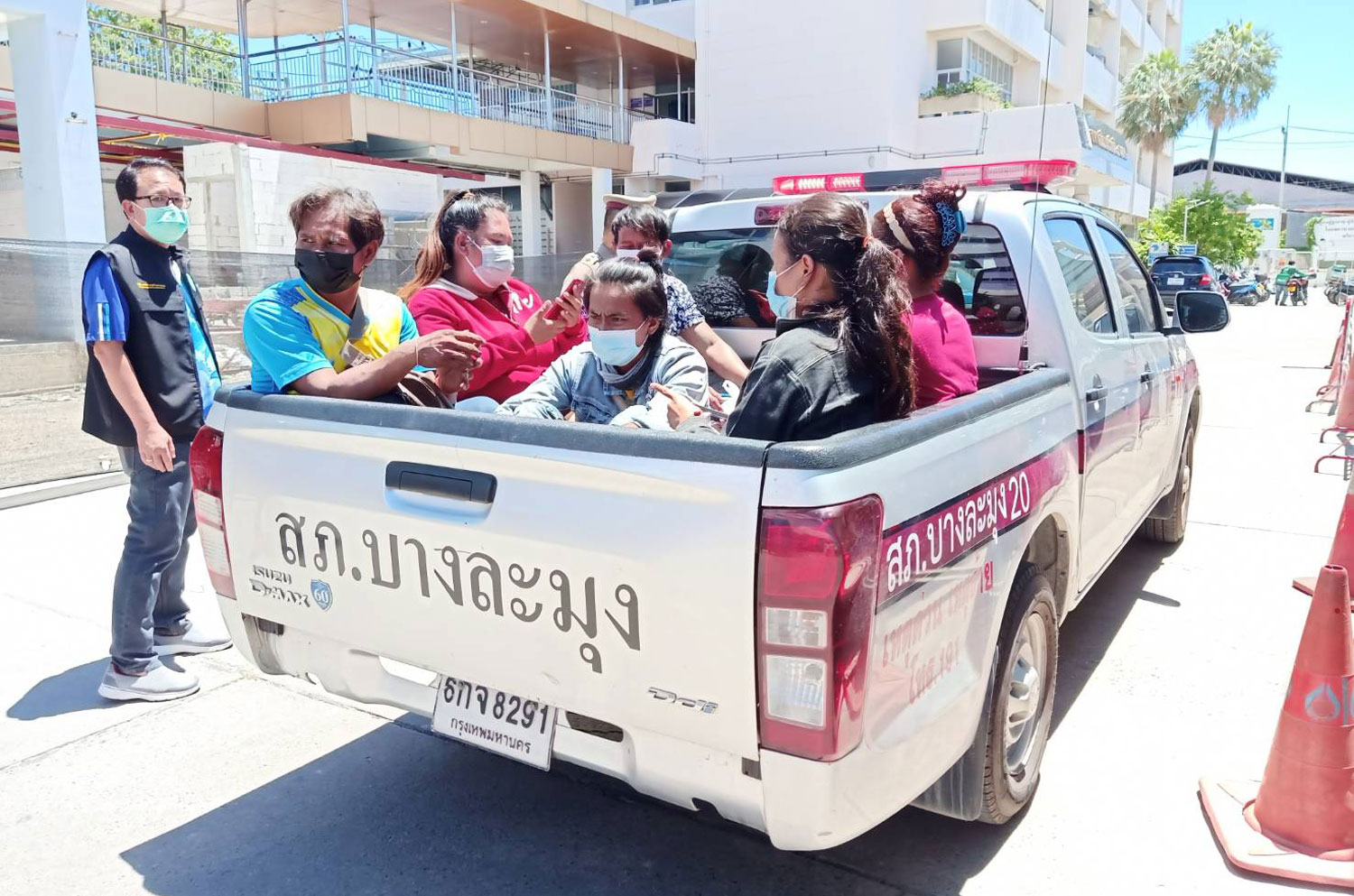 Subcontractor Suntharee Lakchai (second from left in police pickup) and her workers are taken to Bang Lamung police station in Chon Buri to face charges of defying a ban on movement of workers. (Photo: Chaiyot Pupattanapong)