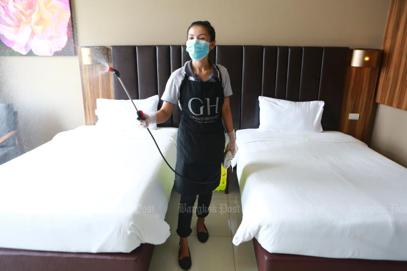 A woman disinfects a room at Grand Howard Hotel to be used as a hospitel on Monday Bangkok faces a bed shortage. (Photo: Somchai Poomlard)