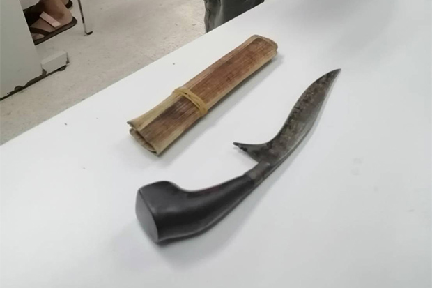 Police show a long knife that Boonyuen Waennak used to kill his own son, said to have gone berserk, in Cha-uat district in Nakhon Si Thammarat on Saturday. (Photo by Nujaree Raekrun)