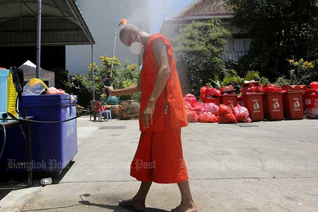 A monk cleans himself after doing chores at Wat Saphan in Bangkok's Klong Toey district. The temple has opened a centre with 150 beds for Covid-19 sufferers before they are referred to medical facilities for treatment.(Photo: Wichan Charoenkiatpakul)