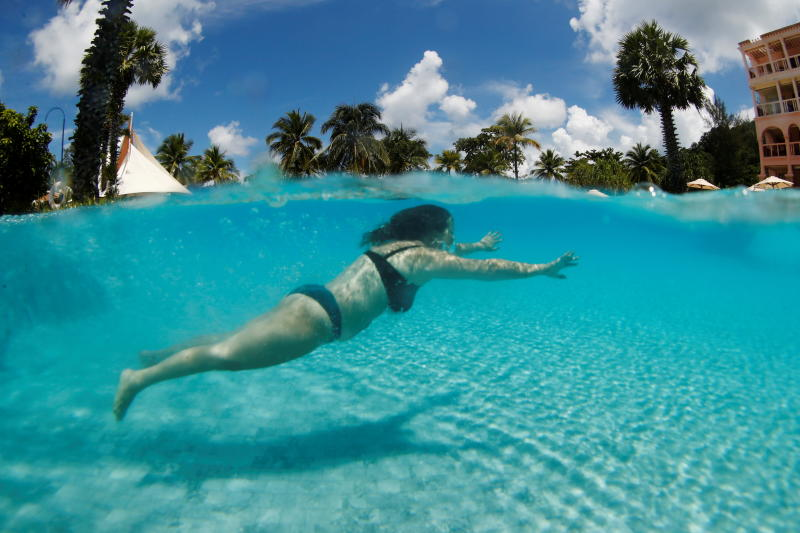 An Israeli tourist is having fun in the pool on Friday, the day after Phuket reopens to foreign tourists.  The country plans to open more destinations for visitors.  (Photo by Reuters)