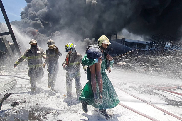 An injured victim is carried away from the flames in a fireman's lift at the burning Ming Dih Chemical factory in Bang Phli district, Samut Prakan, on Monday. One rescuer  died fighting the blaze and at least 60 people were injured by the massive explosion and subsequent fire. (Rescue foundations photo)