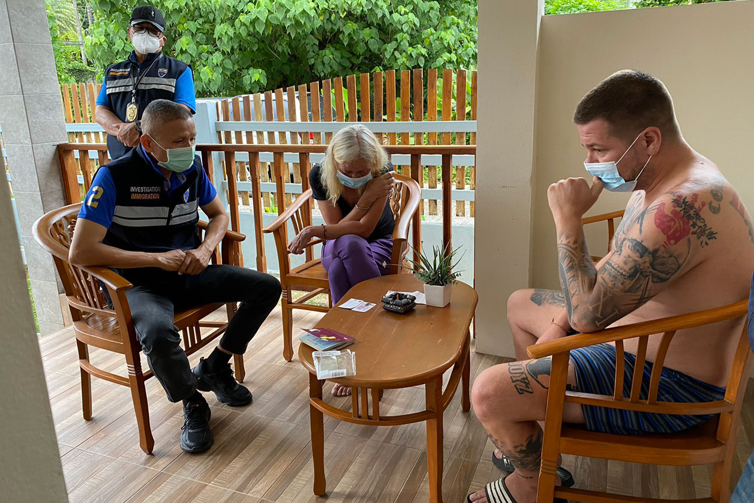 An immigration police officer interrogates one of two German drugs fugitives arrested on Tuesday morning. (Immigration Bureau photo)