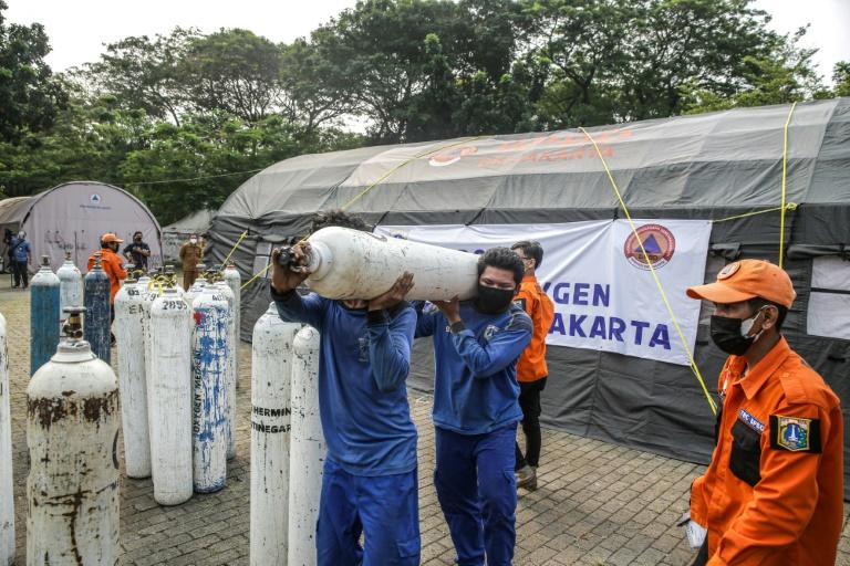 Workers unload oxygen tanks at an emergency oxygen station in Jakarta.