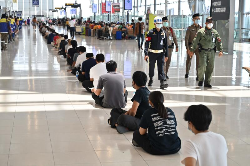 FILE PHOTO: Airport workers wait in a queue to receive vaccinations against the Covid-19 coronavirus while security personnel walk by at the departure terminal of Suvarnabhumi Airport in Samut Prakan on June 30, 2021. (AFP)  Close  Selected