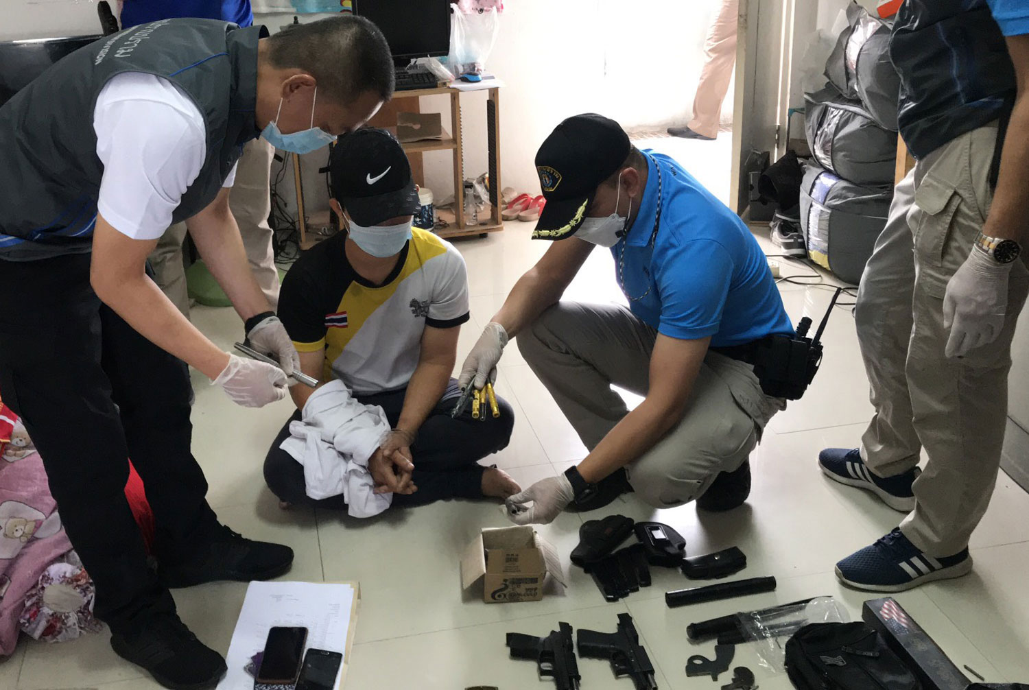 Suspect Prajak Phoonphian, 39, seated and handcuffed, after his arrest at his factory dormitory room in Nonthaburi's Pak Kret district on Thursday morning. (Photo supplied)