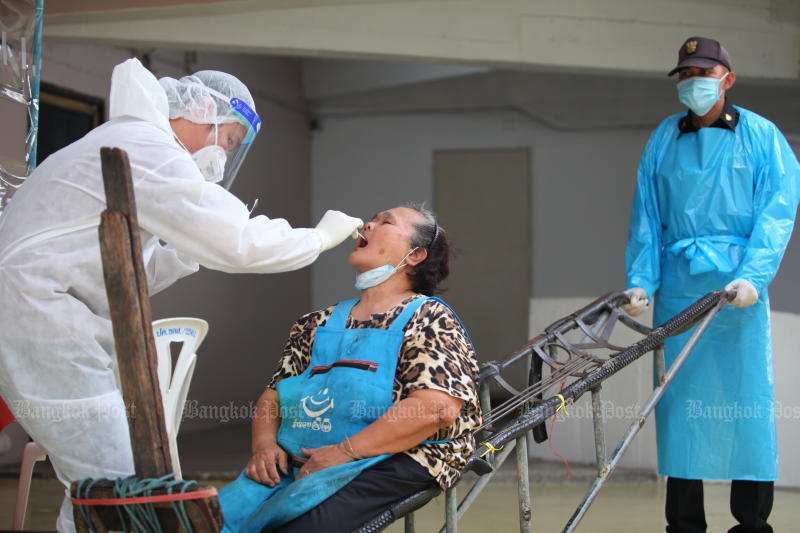 A health worker takes a swab from a woman at Mahanak market in Dusit district on Friday. More testing centres will be opened in Greater Bangkok. (Photo by Apichart Jinakul)