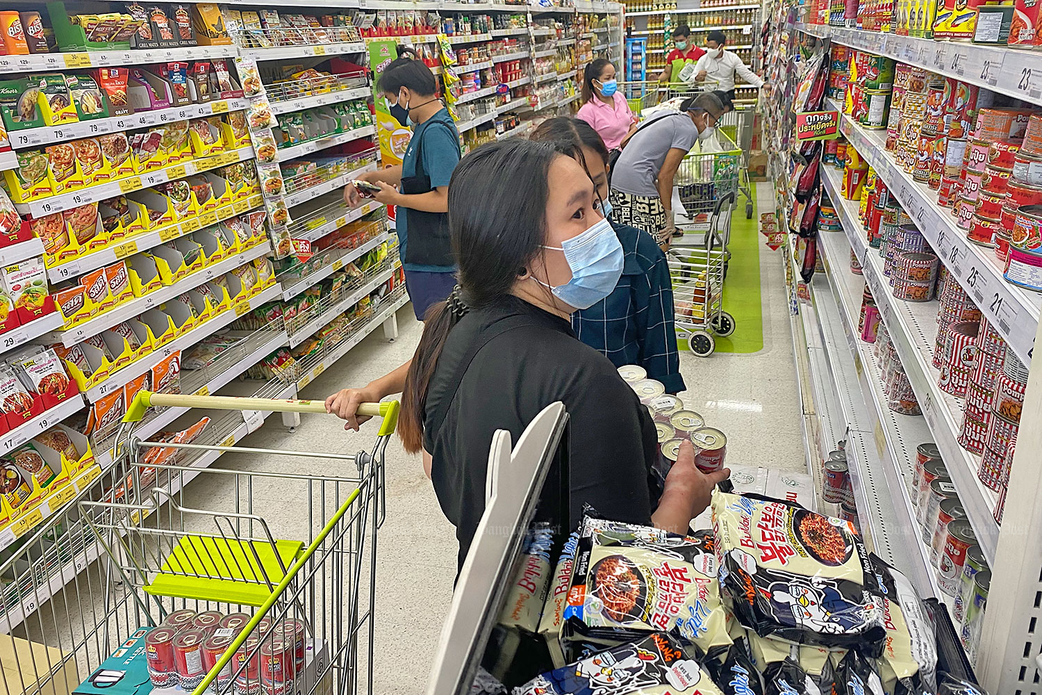 Canning up for the curfew: Women select canned food at a Big C hypermarket in Bangkok's Saphan Khwai area. Consumers in the capital flocked to supermarkets yesterday to shop for essential items after the Centre for Covid-19 Situation Administration decided to impose a curfew and restrict people's movements for 14 days. (Photo: Nutthawat Wicheanbut)