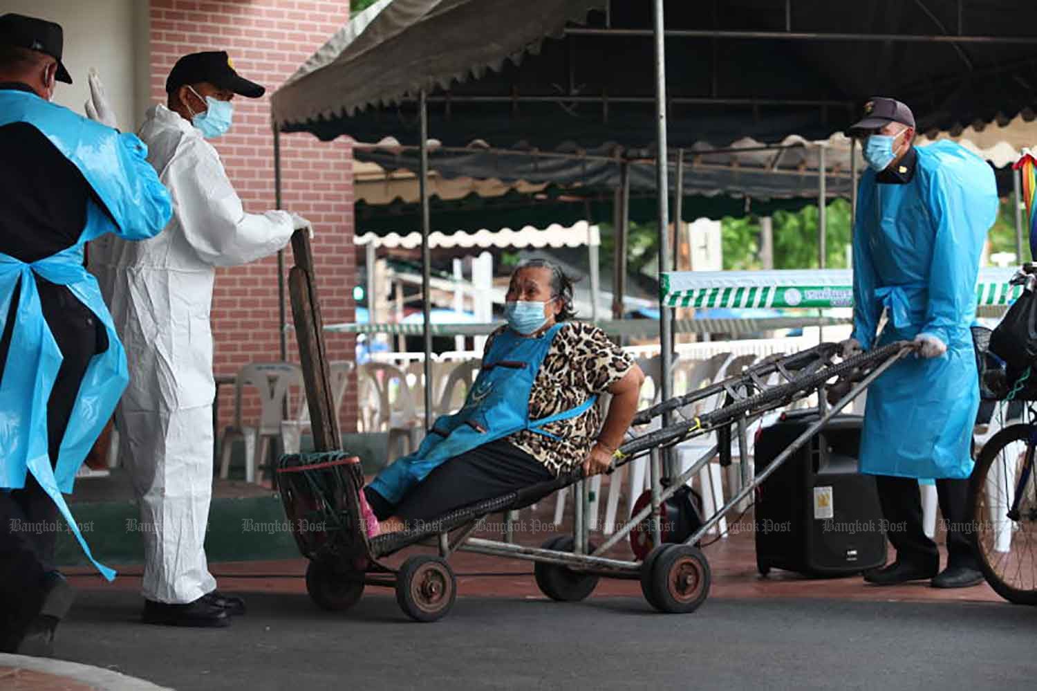Medical workers use a handcart to move an elderly woman to a Covid testing site located in Mahanak fresh market in Bangkok's Dusit district on Friday. (Photo: Apichart Jinakul)