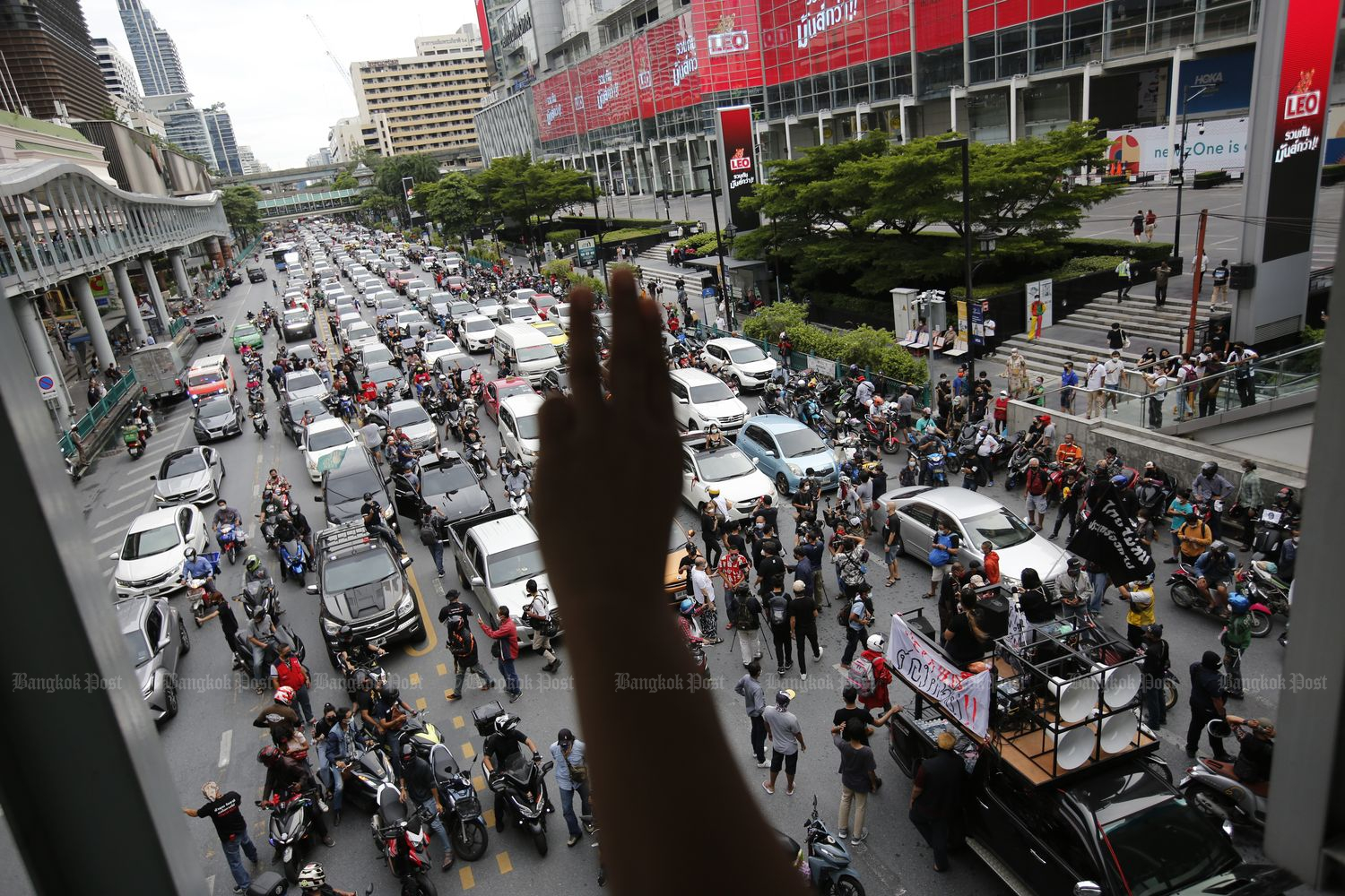 A person flashes a three-fingered salute on the skywalk at Ratchadamri intersection in Bangkok in support of the