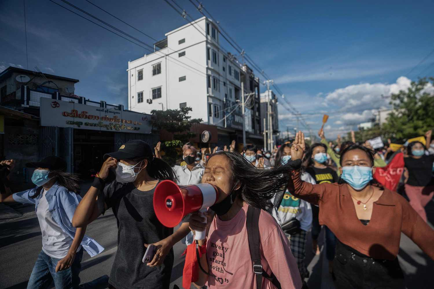 Protesters shout slogans and make the three-finger salute as they take part in a demonstration against the military in Mandalay on Saturday. (Stringer via AFP)