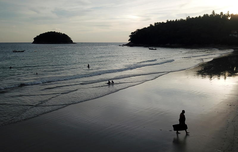People enjoy the evening at almost empty Kata beach as Phuket reopens to overseas tourists on July 1, 2021. (Reuters photo)